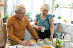Cheerful married couple preparing to eat cereals for breakfast royalty free stock photography