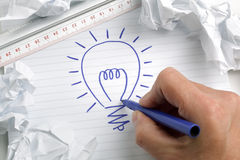 Having a bright idea. Businessmans hand drawing a light bulb, concept for brainstorming and inspiration stock photography