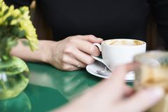 Having coffee in a cafe with flowers on table, close-up shot daylight. Royalty Free Stock Image