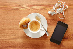 Having coffee and croissants with smartphone Stock Images