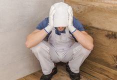 Having Construction Problems. Devastated Home Finishing Worker in a Bathroom Corner. Interior Construction Went Wrong. Caucasian Men Having Job Problems stock photo