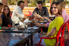 Having drinks and snacks at a bar. Young women hanging out with some friends at a restaurant outdoors Royalty Free Stock Photo