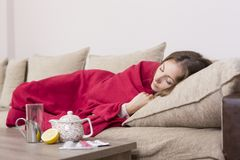 Having fever. Sick woman covered with a blanket lying in bed with high fever and a flu. Pills, teapot and lemon on the table Stock Photo