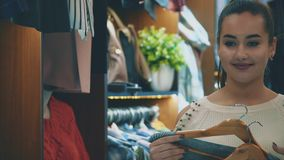 Having found the things she liked, she raises them to her body and enjoys the mirror looking at him. The young girl went shopping for shopping. Having found the stock footage