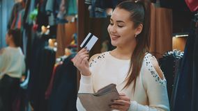 Having found things that liked the young girl in the store she decided to buy them. Taking wallets she found a credit card, rejoicing in it kisses her stock footage