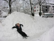Having fun. Child having fun in the snow covered streets. Winter in Munich, Bavaria is fun royalty free stock photo