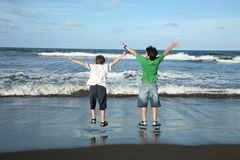 Having fun. Two kids having fun in front the beach Royalty Free Stock Images