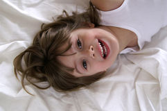 Having fun. A young girl playing in the sheets royalty free stock images