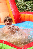 Having fun. Young boy on a water slide royalty free stock photography
