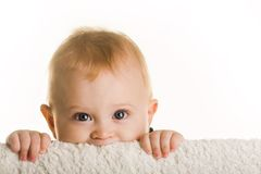 Having fun. Face of curious baby peeping out of board over white background royalty free stock photo