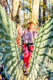Having fun in adventure park. Little girl is climbing in adventure park Royalty Free Stock Photography