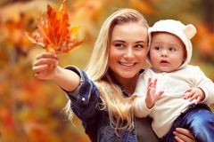 Having fun in autumn park. Portrait of a happy mother holding on hands her precious little son and showing to him dry maple leaves, having fun in the autumn park Royalty Free Stock Image