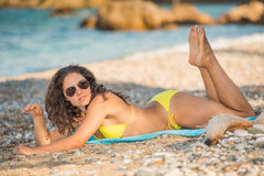Having fun on the beach. Young and attractive woman in sunglasses and yellow bikini lying on the beach with her legs and feet up royalty free stock image