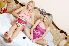 Having fun 2 beautiful blonde young sisters girl friends sitting together watching movie in pajamas. Two blonds young pretty women cute sibling sisters sitting Royalty Free Stock Image