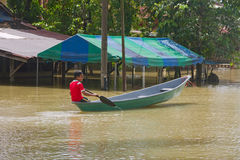 Having Fun with boat in Flood. A boy having fun with boat in the flood water. Heavy rains cause irregular flood in Rantau Panjang, Malaysia - Thai borders Royalty Free Stock Images