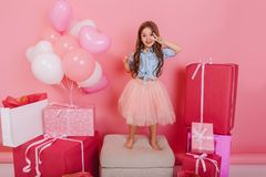 Having fun of cute pretty birthday kid in tulle skirt dancing on chair suround a lot of giftboxes, balloons  on