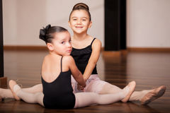 Having fun at dance class. Cute little girls having fun and holding hands while doing some stretching exercises during a ballet class Royalty Free Stock Photography