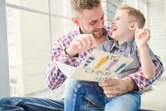 Having Fun on Fathers Day. Adorable little boy and his bearded dad having fun together while reading handmade greeting card for Fathers Day aloud, panoramic Stock Image
