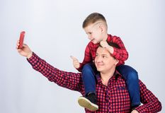 Having fun. Fathers day. Father example of noble human. Father little son red shirts family look outfit. Taking selfie. With son. Child riding on dads shoulders royalty free stock image