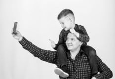 Having fun. Fathers day. Father example of noble human. Father little son red shirts family look outfit. Taking selfie. With son. Child riding on dads shoulders stock photography