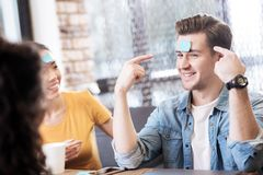 Happy man playing a game with his friends. Having fun. Handsome joyful young men smiling and pointing at the sticker on his forehead while playing a game with Royalty Free Stock Photos