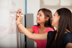 Having fun at high school. Cute high school friends laughing and having fun while solving a problem on a white board royalty free stock images