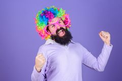 Having fun. Holiday fun and carnival concept. Man bearded wear colorful wig and funny glasses on violet background. Clown and circus. Party fun. Enjoy being stock image