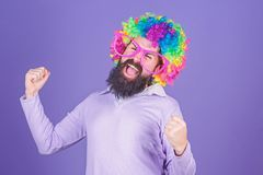 Having fun. Holiday fun and carnival concept. Man bearded wear colorful wig and funny glasses on violet background. Clown and circus. Party fun. Enjoy being stock photography