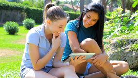 Having fun with ipad tablet in park. Two young women looking social network with tablet stock video