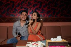 Having Fun in Karaoke. Joyful young couple having fun in karaoke night club: they sitting on cozy sofa and holding microphones in hands while waiting for Stock Photo