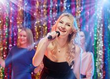 Having fun at karaoke. Portrait of young pretty blonde women singing at karaoke with her girlfriends Royalty Free Stock Photos