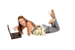 Having fun with laptop. A young tall woman lying on the floor and looking at her laptop, in jeans high heels and long brunette hair, for white background royalty free stock photos