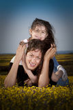 Having fun with mom. Little girl on the back of her mom having fun in a field of yellow flowers Stock Image