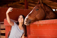 Having fun with my horse. Beautiful young Hispanic woman taking a photo of herself and her horse at the stables stock photography