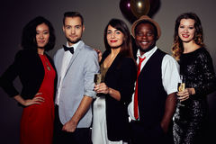 Having Fun in Office Christmas Party. Multi-ethnic group of colleagues with champagne flutes in hands posing for photography while having office Christmas party Stock Photo
