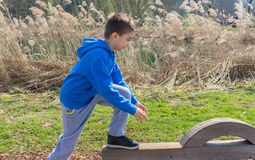 Having fun outdoors. Young boy climbing on playground Stock Photography