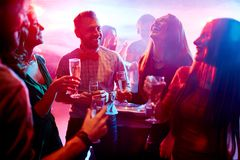 Having fun at party. Ecstatic friends with champagne talking at party in night club royalty free stock photos