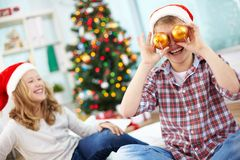 Having fun. Portrait of happy lad holding decorative toy balls by his eyes and laughing on Christmas evening Royalty Free Stock Photo