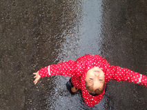Having fun a rain day on street. Pretty little girl having fun a rain day on street royalty free stock photography