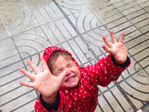 Having fun a rain day on street. Pretty little girl having fun a rain day on street royalty free stock images