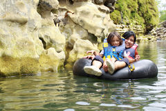 Having fun in the river. Happy mother and son floating on inflatable tube in river during vacation Stock Photo
