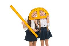 Having fun in school. Pupil cute girls with big rulers. School children with measuring instruments. Geometry favorite. Subject. Education and school concept royalty free stock image