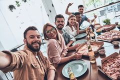 Having fun. Self portrait of young people in casual wear smiling and looking at camera while having a dinner party royalty free stock image