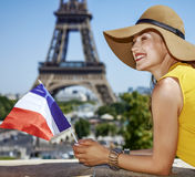 Happy woman with French flag in front of Eiffel tower in Paris Stock Image