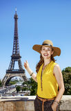 Happy woman pointing on Eiffel tower in Paris. Having fun time near the world famous landmark in Paris. Portrait of happy young woman in bright blouse pointing Stock Image