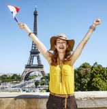 Happy young woman rising flag in front of Eiffel tower in Paris Stock Image