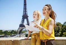 Mother and child tourists holding map and pointing. Paris. Having fun time near the world famous landmark in Paris. smiling mother and child tourists holding map Royalty Free Stock Photography
