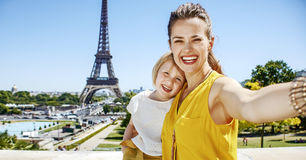 Mother and child tourists taking selfie against Eiffel tower. Having fun time near the world famous landmark in Paris. smiling mother and child tourists taking Royalty Free Stock Images