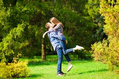 Having fun together. Beautiful young loving couple standing outdoors together while woman hugging her boyfriend. Having fun together. Beautiful young loving stock image