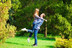 Having fun together. Beautiful young loving couple standing outdoors together while woman hugging her boyfriend. Having fun together. Beautiful young loving stock photo